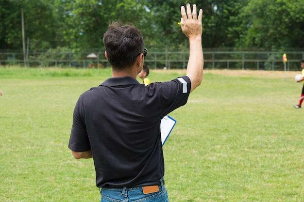 Менеджер команды тренирует свою команду возле футбольного или футбольного поля