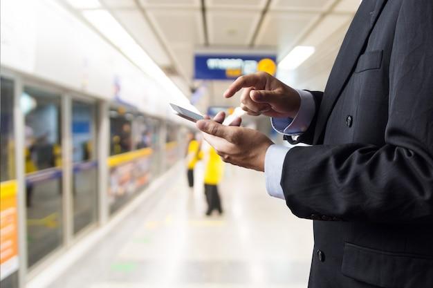 ビジネスマンの手がワイヤレスデジタルスマートデバイスまたはスマートフォンを保持します。