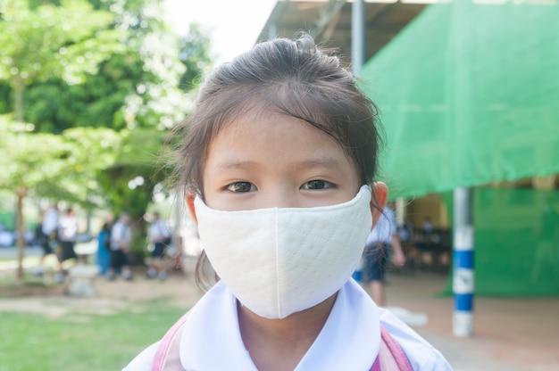 フェイスマスクとアジアの小さな女の子の学生は学校に行く