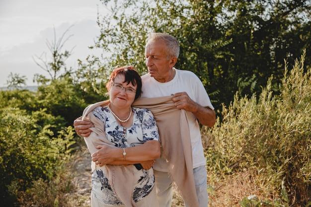 年配の男性が夏の森の散歩でショールで妻の肩を覆っています