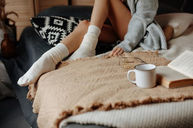 Урожай женщины, ноги, чашка кофе и книга на кровати