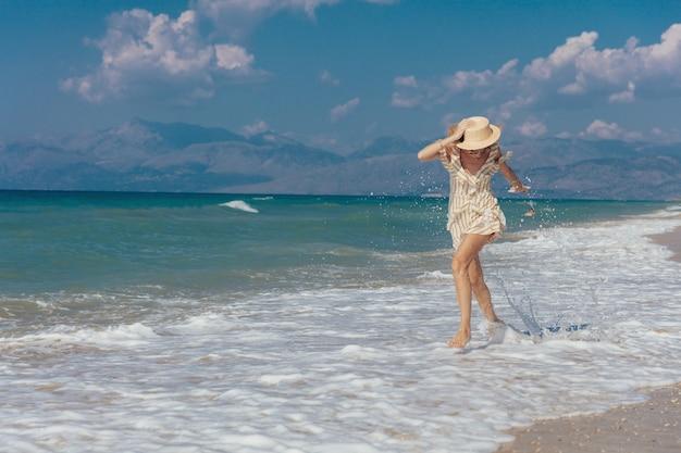 砂浜で裸足で歩く陽気な美しい少女