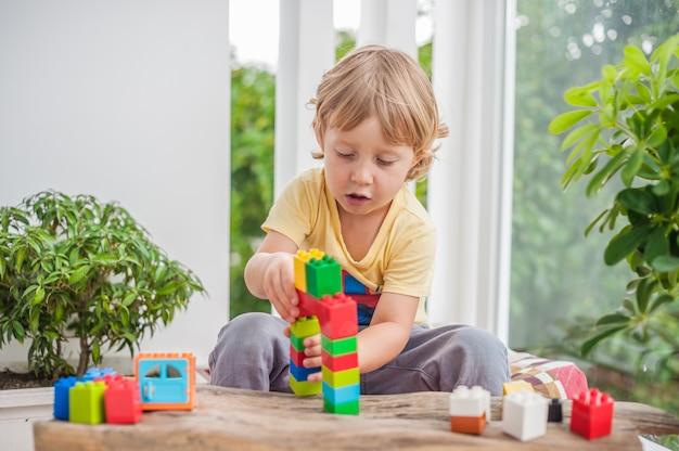 Маленький мальчик с игрой с красочными пластиковыми блоками в помещении