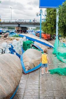 Мальчик смотрит на голубую бухту с лодки