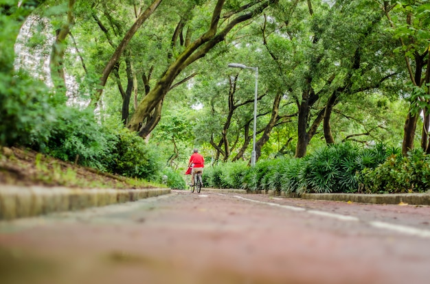 Человек катается на велосипеде в парке