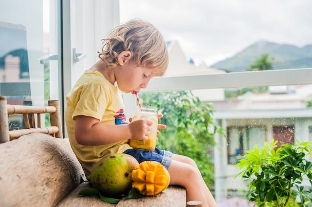ストライプの赤いストローでガラスの石工の瓶にマンゴーからジューシーなスムージーを飲む少年