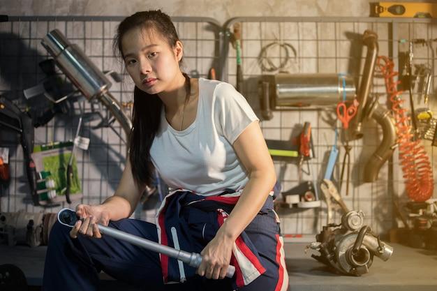 Женщина подготавливая ключ для работы в гараже. концепция работы и починки дома.