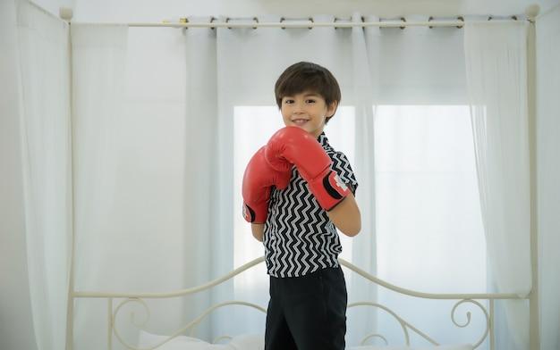 ボーイショーボクシングはベッドにパンチミットを持っています。
