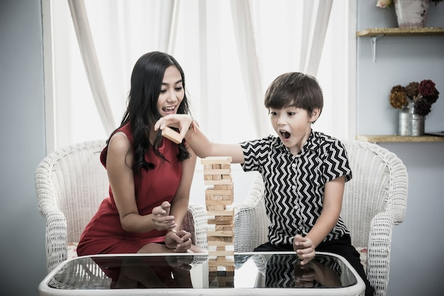 母と息子はジェンガゲームをしています。幸せな家族。