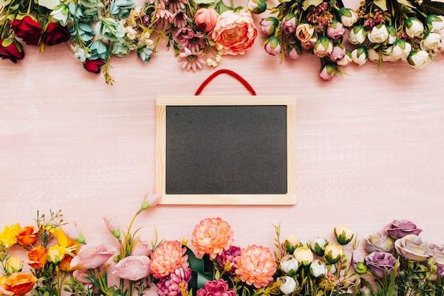 花と木製の背景に黒板