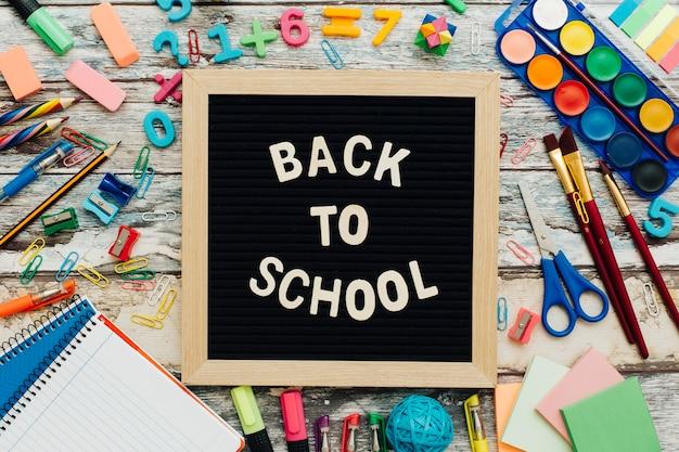 Слова «снова в школу», написанные на меле на школьном столе с крупными школьными принадлежностями.