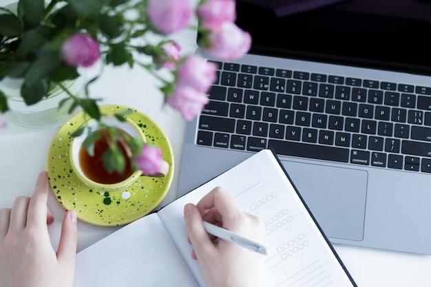 ホームオフィスの職場。ノートパソコンで職場でノートに書く作業スケジュールを計画する女性。