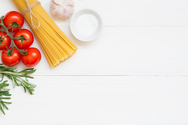 スパゲッティ成分、トマト、ローズマリー、塩、ニンニクの概念白い背景の上