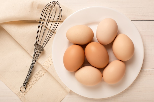 茶色の卵と白いテーブル、食材、上面に泡立て器でプレート