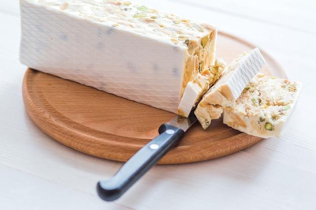 イタリアのトローネまたは白い木製のテーブルにアーモンドとヌガー、選択したフォーカスでクローズアップ、クローズアップ
