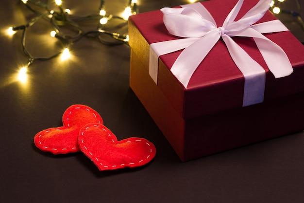 Красная подарочная коробка и сердца крупным планом на черном фоне с огнями