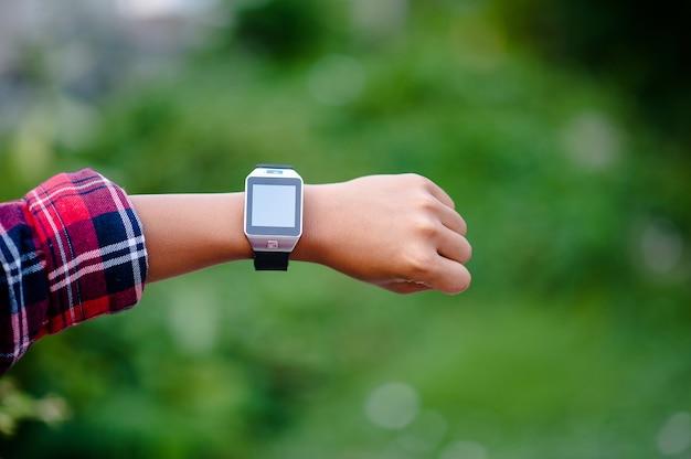 男の子の手やデジタル時計腕時計を見る。方向は定刻です。