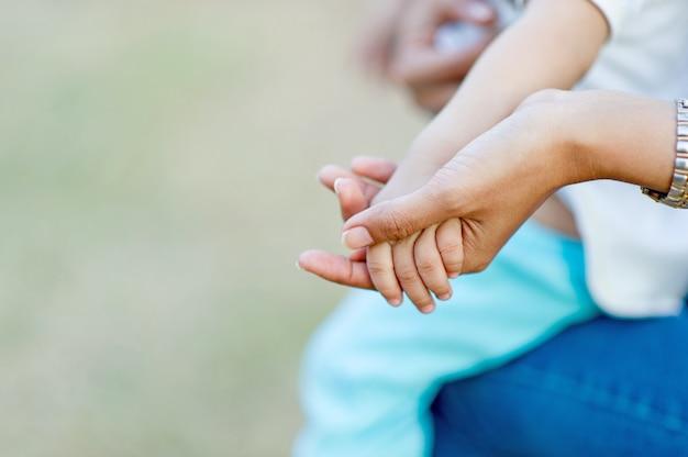 母親の愛によって捉えられた母親の手と赤ちゃんの写真コピースペースを持つ母親と子供のコンセプト