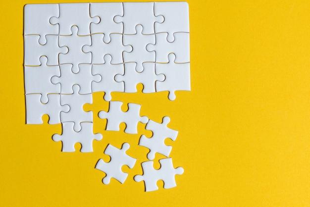 黄色の背景に置かれたジグソーパズルコピースペースを持つ創造的な概念
