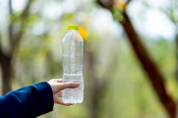 手と水のボトル飲料水コピースペースと創造的な概念