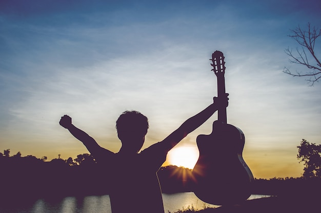 夕日の光、シルエットの概念で影にギタリストのシルエット。