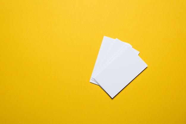 ビジネスマンの名刺は黄色の背景に配置されます。コピースペースを持つビジネスコンセプト