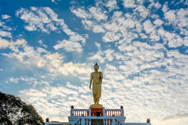 立っている仏像そして青い空、宗教的な概念