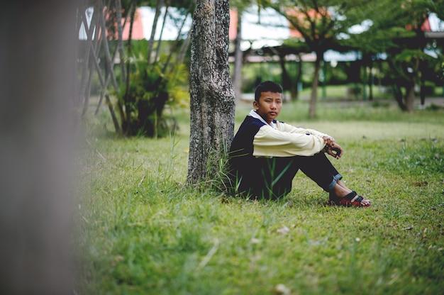 悲しいことに森の中で一人で座っている少年の写真うつ病の概念