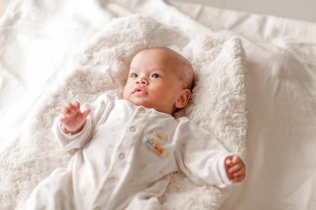 Милый малыш в спальне с белым светом.