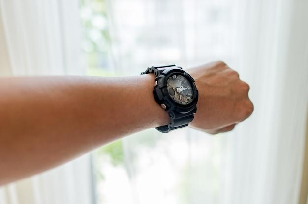 時間の概念が好きな若い男性の手と黒の腕時計