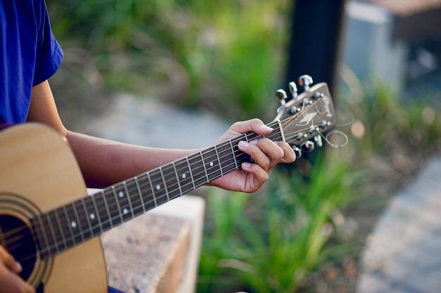 ギターのコンセプト、楽器を演奏するギタリストの手とギター