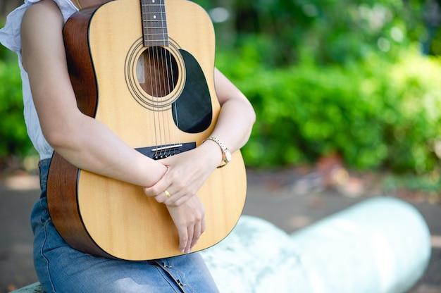 ミュージシャンの手とアコースティックギター、非常に良い音の楽器
