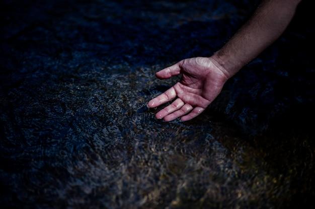 自然の滝から流れる手と水自然の滝からの水の概念