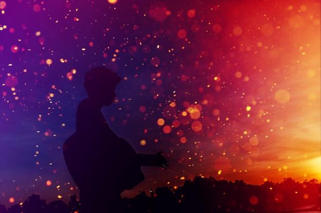 夕日の光、シルエットの概念で影でギタリストのシルエット。