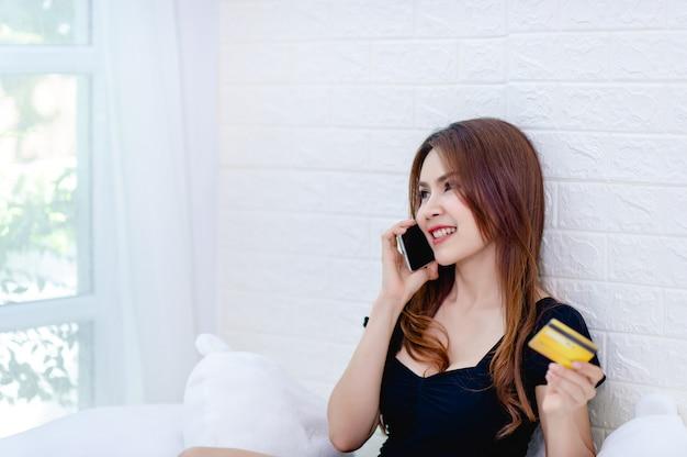 ビジネスの女性は電話で話し、クレジットカードを見て