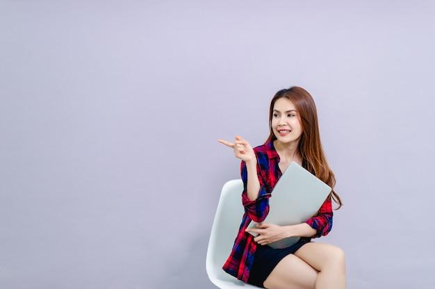 女性とラップトップ職場で楽しくラップトップを座って抱きしめる