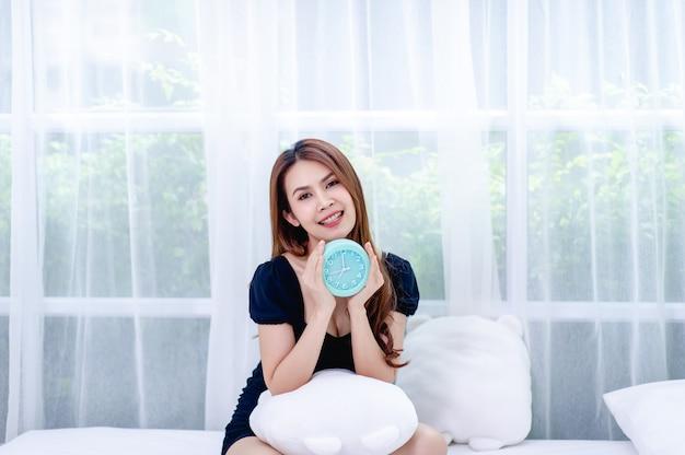 Женщина и синий будильник в спальне концепция релаксации