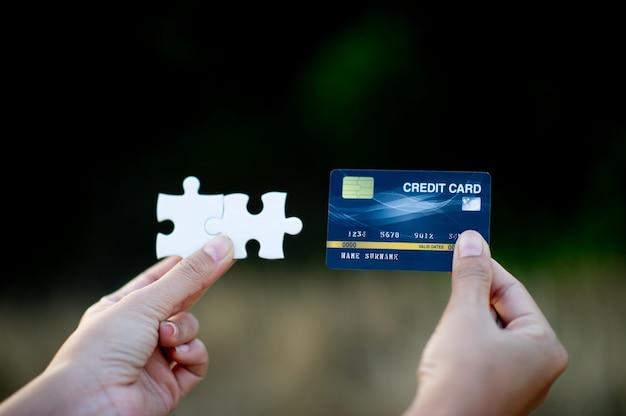 白いジグソーパズルのピースとクレジットカードを保持している手