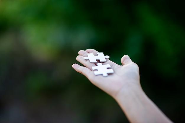 手と白いジグソーパズルのピース