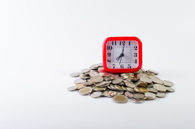 Деньги, бат монеты на белом фоне и красные часы