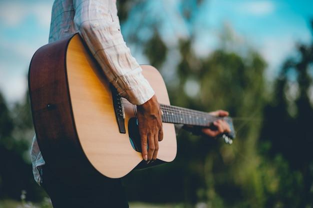 男の手はアコースティックギターを演奏し、庭だけでギターを演奏する