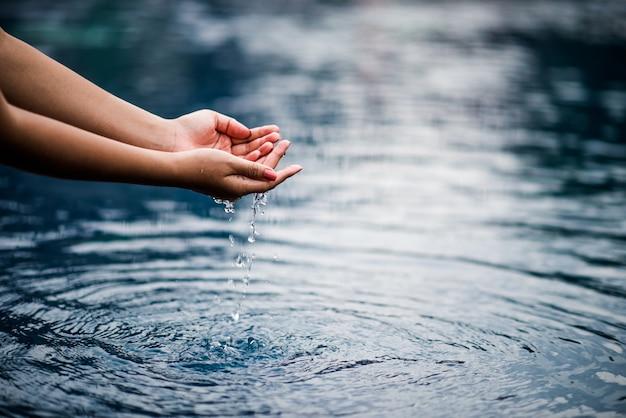 青い水に触れる手。