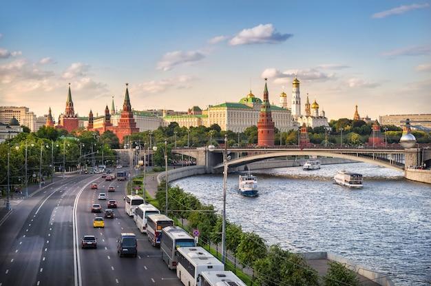Вид на башни, храмы московского кремля и машины на набережной
