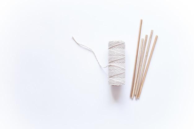 白い表面にマクラメ織りのツールと素材。綿のロープとスティック。
