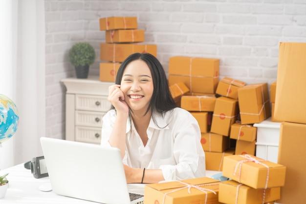 幸せな若いアジアの女性は、オンラインショッピングのための中小企業の懸念がある