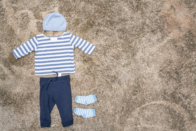 赤ちゃんの服は洗濯ラインと木製の背景で乾燥していた