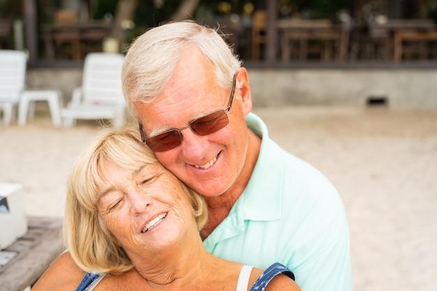 年配のカップルが一緒にビーチに座っています。