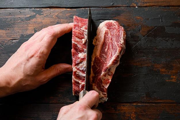 肉屋の手で肉を半分に切るステーキのトップビュー