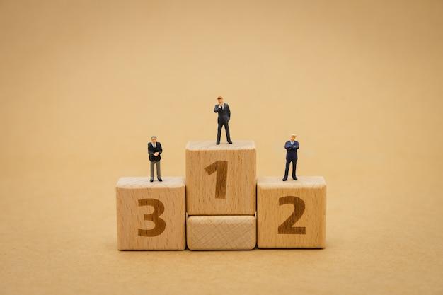 ミニチュアのビジネスマンが表彰台に上がることに立っています。