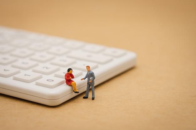 背景としてビジネスコンセプトを使用して白い電卓の上に座ってミニチュア人
